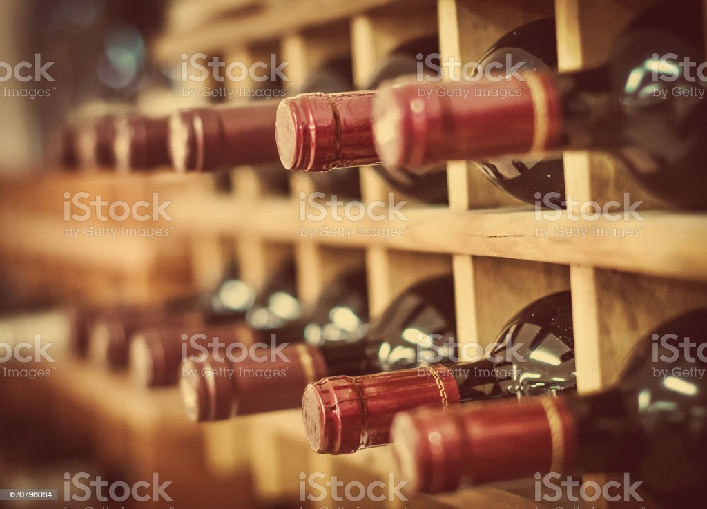 Red wine bottles stacked on wooden racks stock photo