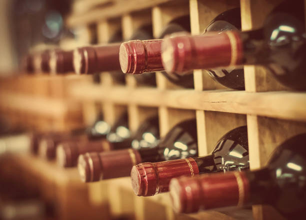 Red wine bottles stacked on wooden racks - Photo