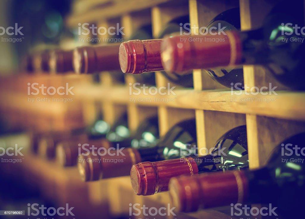 Red wine bottles stacked on wooden racks – Foto