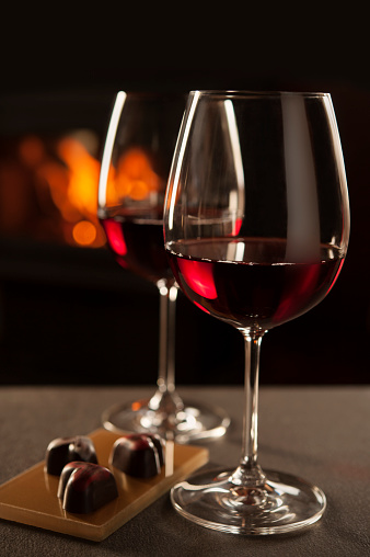Two glasses of red wine backlit by a fireplace, along with heart shaped chocolates for a romantic evening.