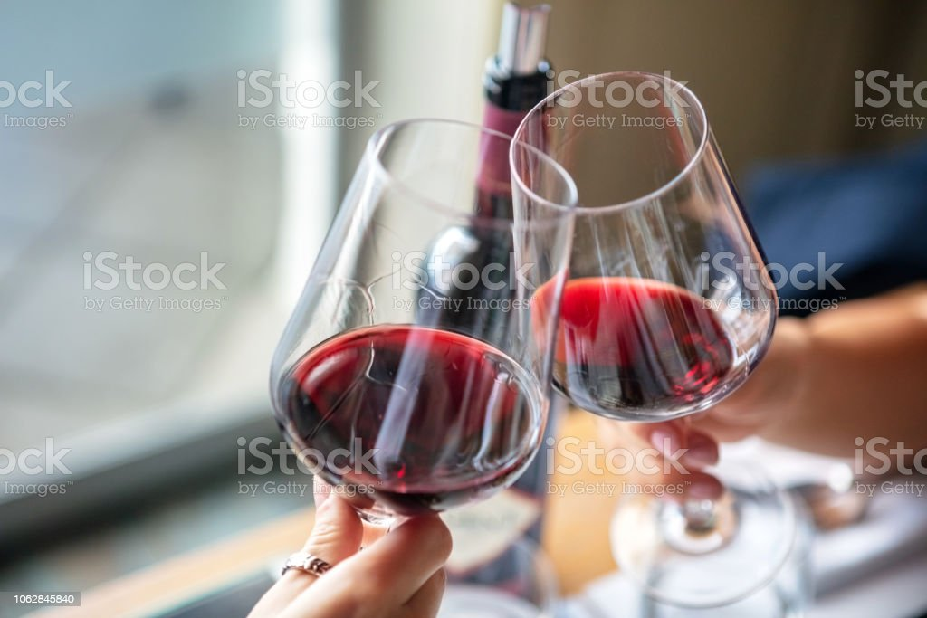 Red wine celebratory toast Elevated view of celebratory red wine toast Adult Stock Photo