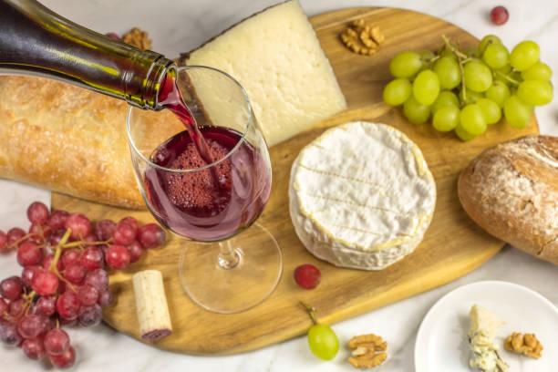 red wine, cheese, bread and grapes at tasting - dinge die zusammenpassen stock-fotos und bilder