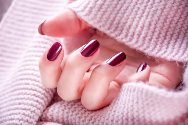 wein rot maniküre auf der mädchen seite - herbst nagellack stock-fotos und bilder