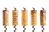 Five different red wine corks and corkscrew isolated on white.