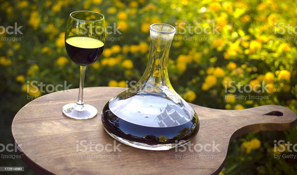 Red Wine Decanter & Wineglass, Romantic Outdoor Spring Picnic Table stock photo