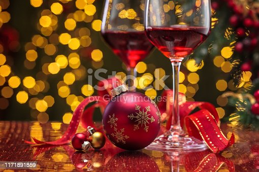 Red wine in wineglasses and Christmas ball against holiday lights background.