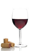 red wine glass and corks on white background
