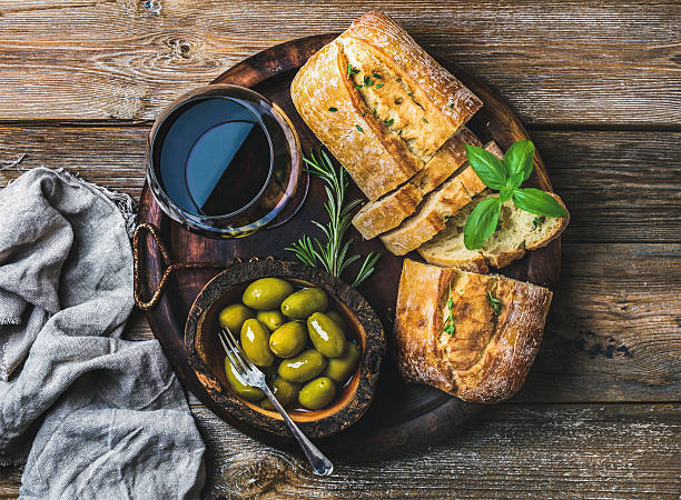 Red wine glass, green olives and ciabatta over wooden background stock photo
