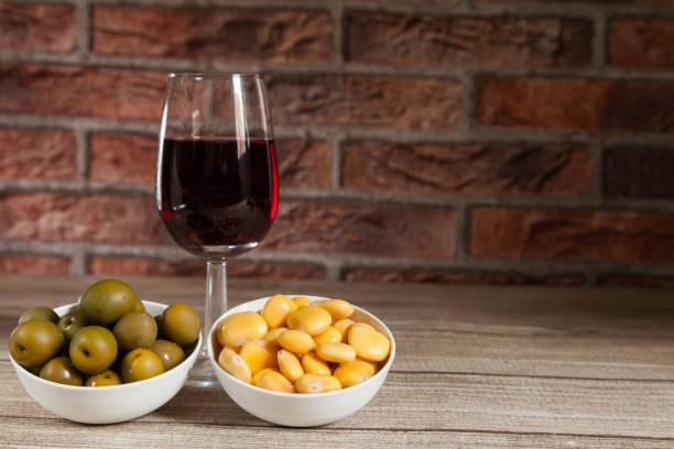 Copa de vino tinto, cuenco de aceitunas y tazón de alpins - foto de stock