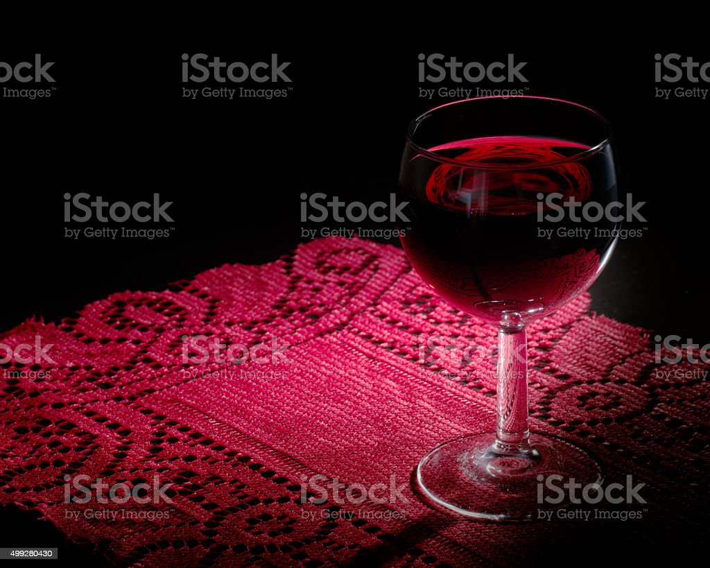 Red wine glass on lace stock photo