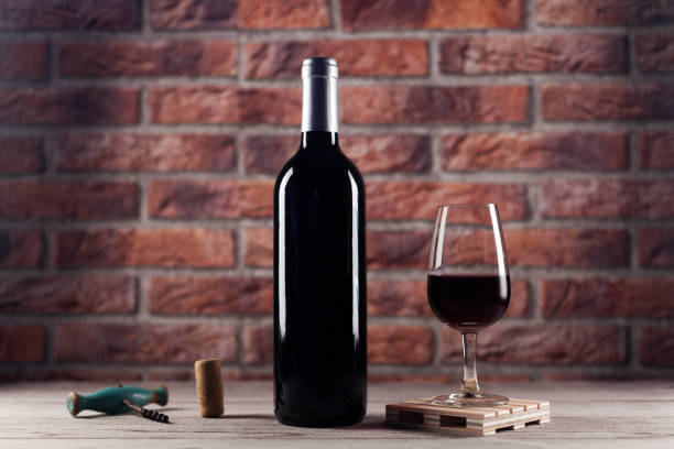 red wine glass red wine glass on mini pallet, bottle, cork and  corkscrew on wood table and bricks background merlot grape stock pictures, royalty-free photos & images
