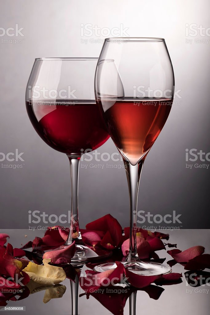 Red wine glass, rose wine glass and rose-petals on black stock photo