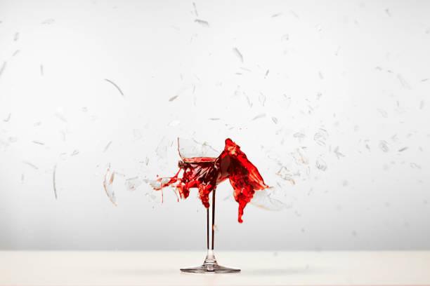 Red wine glass smashing stock photo