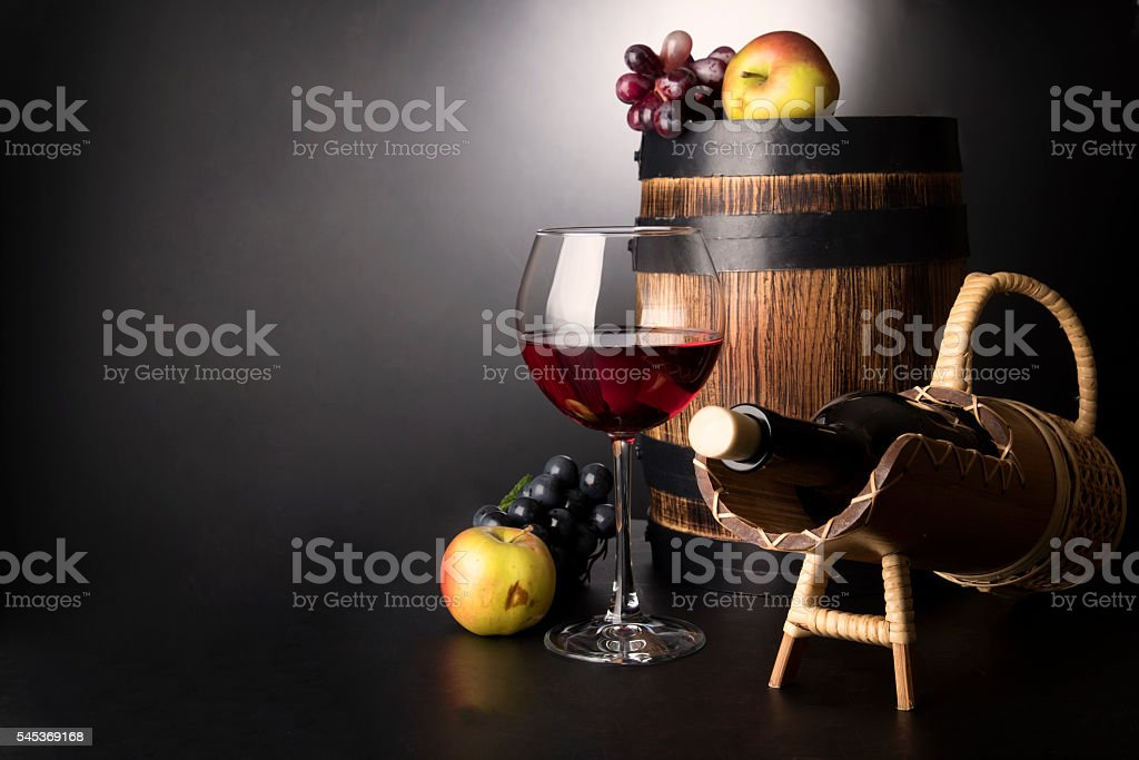 Red wine glass with bottle, wooden and fruits. stock photo