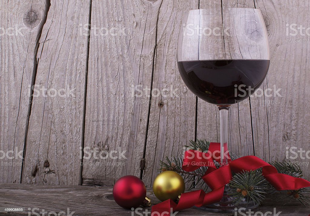 Red wine glass with Christmas decoration on the wooden table stock photo