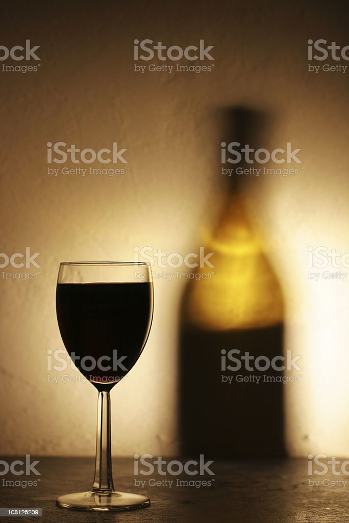 Red Wine Glass with Shadow of Bottle on Stucco Wall royalty-free stock photo