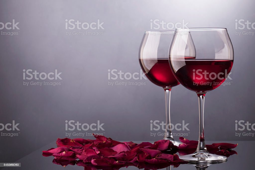 Red wine glasses and rose petals isolated stock photo