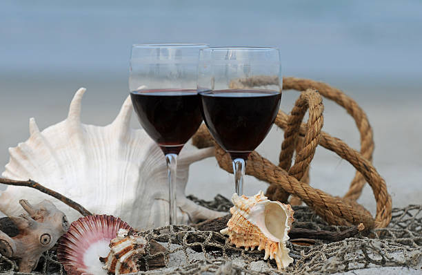 Red Wine Glasses on the Beach Surrounded by Shells stock photo