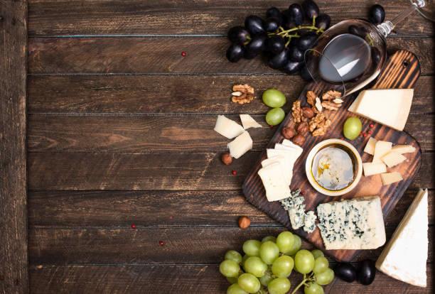 Rotwein, Trauben, Käse, Honig und Nüssen über rustikale Holz. – Foto