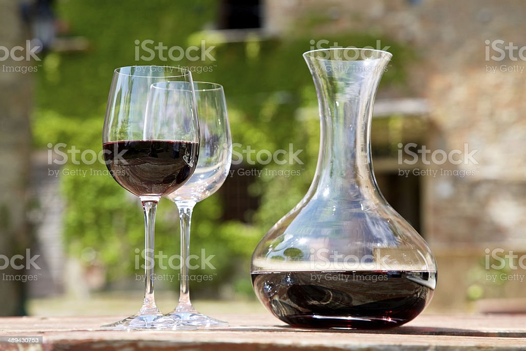 Red wine in a wine carafe and a two wine glasses in old vineyard stock photo