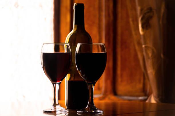 Vinho vermelho em um vidro de vinho com um frasco do vinho, celebração de um momento com um vidro do vinho, licor requintado para gourmets - foto de acervo