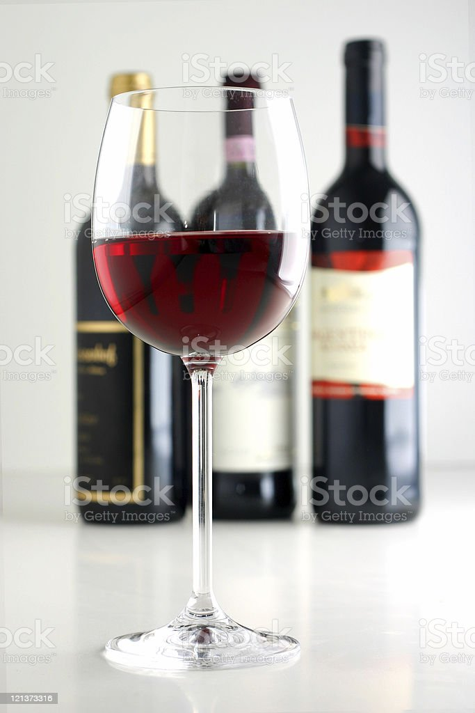 Red Wine in front of three bothhles royalty-free stock photo