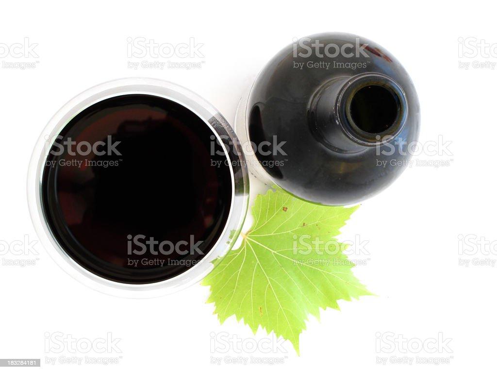 Red wine in glass and a bottle with a green leaf royalty-free stock photo