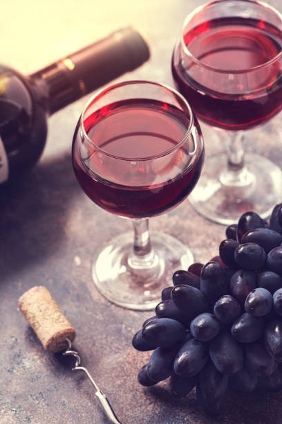 Red wine in glasses in the sunlight, grapes, a bottle, a cork, a corkscrew. Selective focus. Toned photo. Red wine in glasses in the sunlight, grapes, a bottle, a cork, a corkscrew. Selective focus. merlot grape stock pictures, royalty-free photos & images