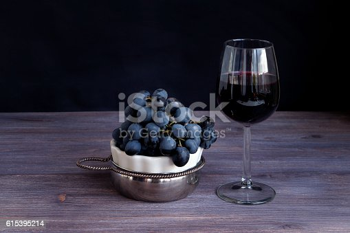 istock Red wine in wine glass, bunch of dark purple grapes 615395214
