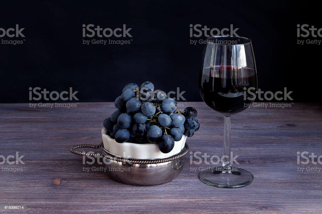 Red wine in wine glass, bunch of dark purple grapes stock photo