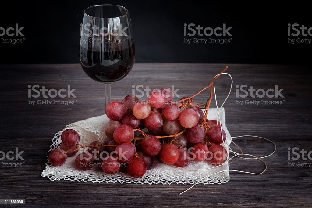 Red wine in wine glassю bunch of pink red grapes stock photo