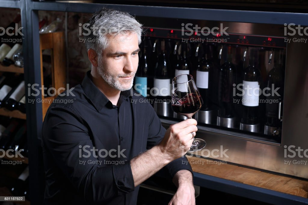 Red wine, man evaluates the color of wine in a glass stock photo