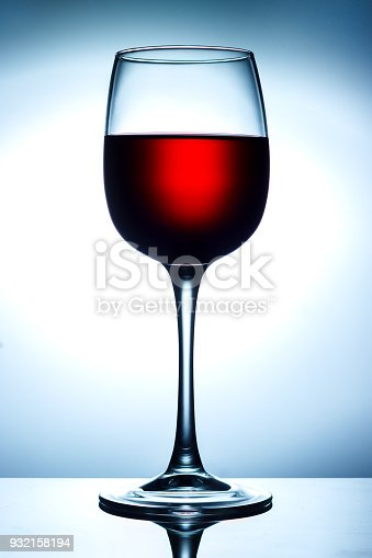 istock Red wine on a skylight with reflection on a blue background 932158194