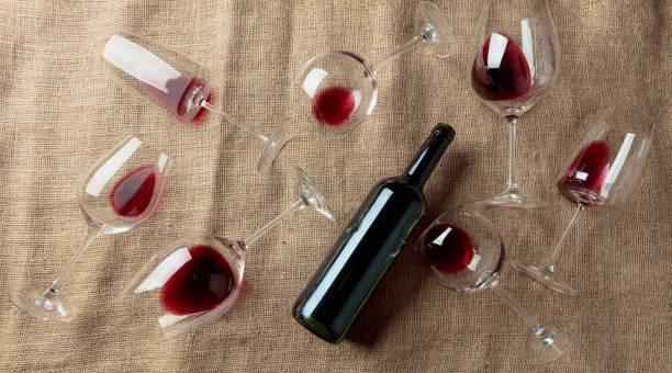 rotwein auf einem tisch, der mit burlap bedeckt ist. - bordeaux wein stock-fotos und bilder
