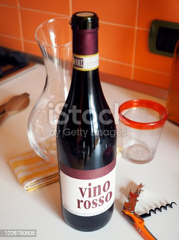 No logo Italian red wine bottle ready to be opened along its empty decanter.
