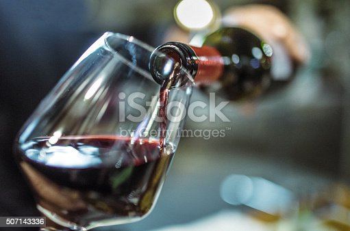 Unrecognizable person, holding a bottle of red wine, is pouring some red wine in a wine glass.