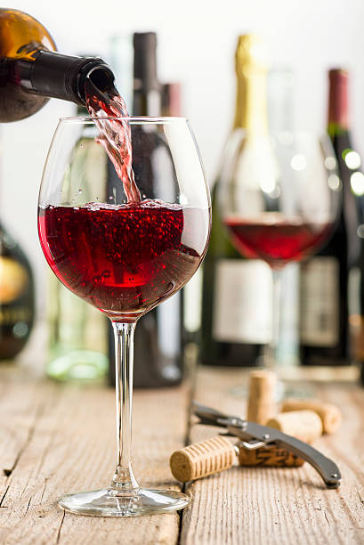 red wine pouring red wine in glass on wooden table near corkscrew and bottle cabernet sauvignon grape stock pictures, royalty-free photos & images