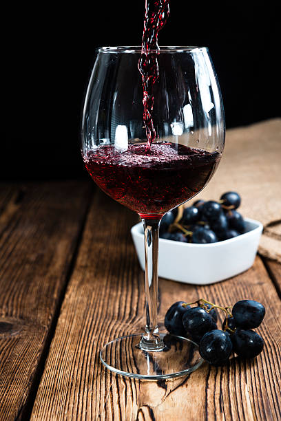 Red Wine (on wooden background) Old vintage wooden table with Red Wine (selective focus) merlot grape stock pictures, royalty-free photos & images