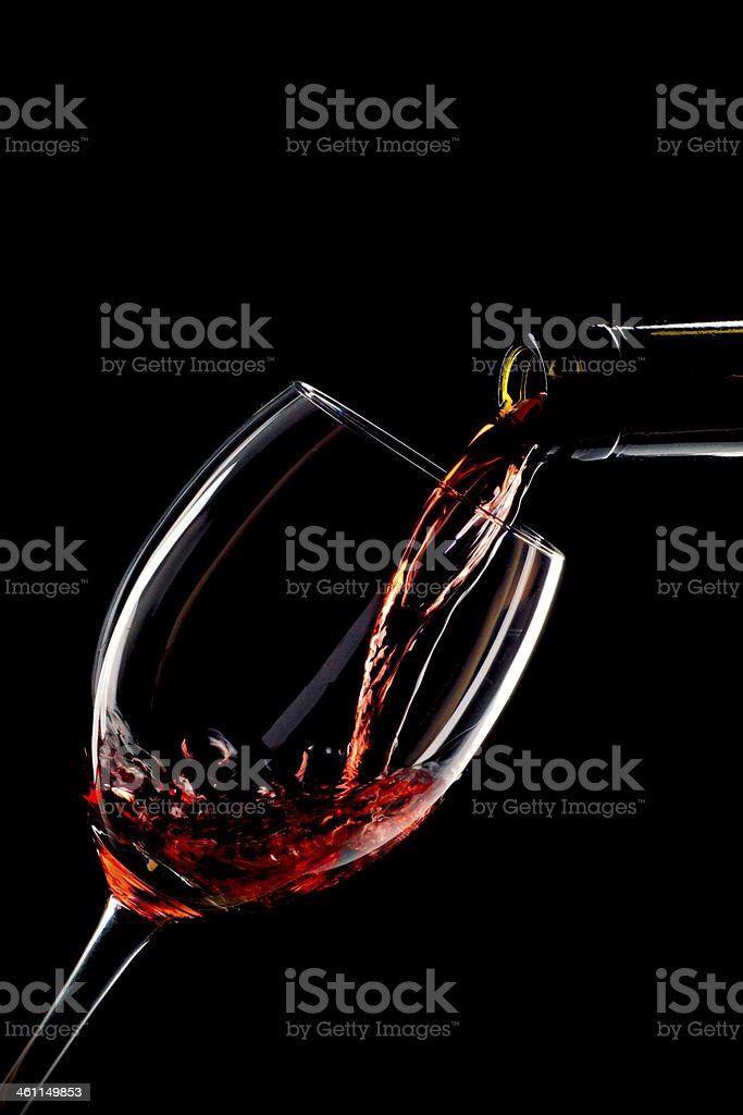 Red wine poured into a glass isolated on black background stock photo