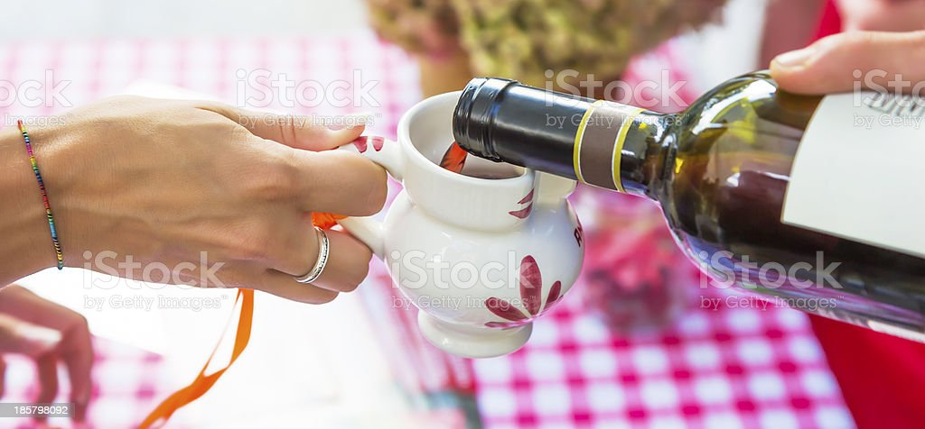 Red wine poured into ceramic jug royalty-free stock photo