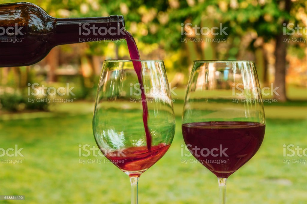 Red wine poured into glass at picnic, with copyspace stock photo