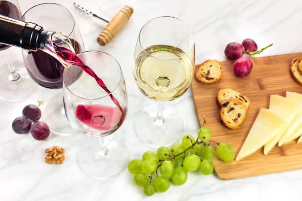 rotwein in glas bei weinprobe mit exemplar gegossen - dinge die zusammenpassen stock-fotos und bilder