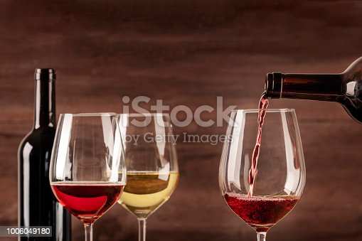 Red wine being poured into a glass from a bottle, on a dark background, with copy space and other glasses in the blurred background. Design template for a tasting invitation