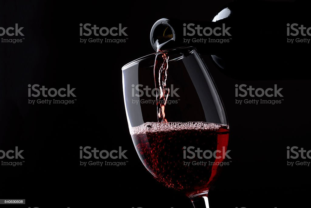Red wine poured into glass stock photo