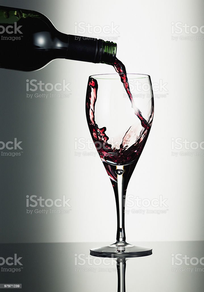 Red wine pouring from bottle into glass royalty-free stock photo
