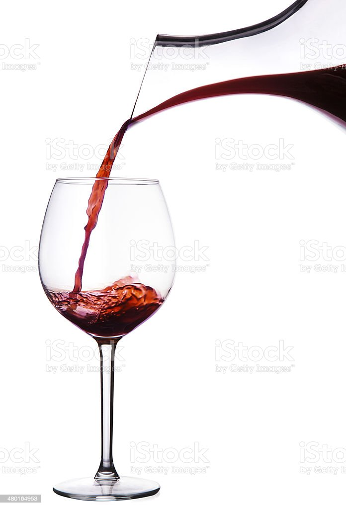 Red wine pouring from decanter into glass. isolated on white stock photo