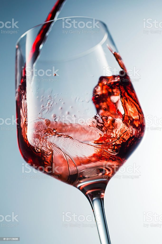 Red wine pouring in glass stock photo