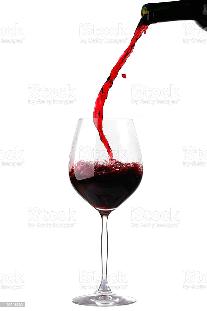 Red wine pouring into a glass against a white background stock photo