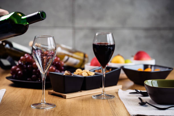 Vino tinto vertiendo en una copa de vino en una degustación con varios tipos de aperitivos. - foto de stock