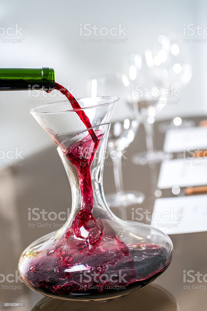 Red wine pouring into decanter at tasting. stock photo